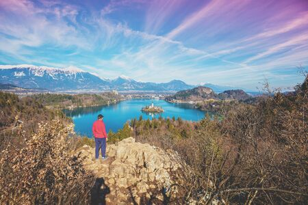 A man standing on a cliff above Lake Bled in early spring. Slovenia, Europe Zdjęcie Seryjne
