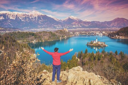 Man with hands in the air standing on a cliff over Bled Lake in early spring. Slovenia, Europe Zdjęcie Seryjne