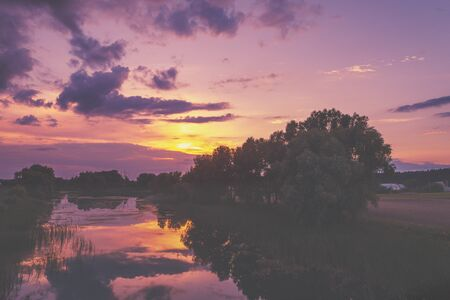 A magical sunset in the countryside. Calm river at sunset. Rural landscape in the evening. Birds-eye view