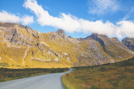 Driving a car on a mountain road in Lofoten islands, view from the windscreen. Norway, Europe