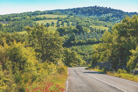 Beautiful landscape, spring nature. Road among sunny fields in Tuscany, Italy