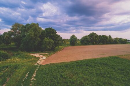 Rural landscape in the evening at sunset.  View from above of plowed field in summer