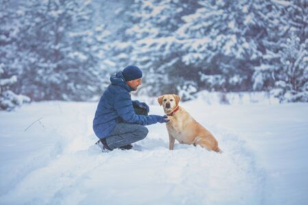 A human and dog are best friends. The man with the dog sitting in a snowy pine wood in winter. Trained Labrador retriever dog extends the paw to the man