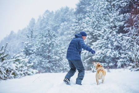 Happy man with labrador retriever dog playing in winter snowy forest