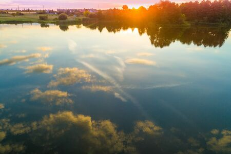 The sunset sky is reflected in the water of the lake. Sunset over the lake