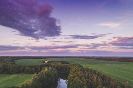 Magical sunset over the countryside. River with trees on the banks. Rural landscape