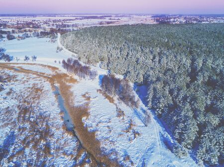 Top view of the winter rural landscape in the evening. Fields covered with snow, forest and frozen creek Stock Photo