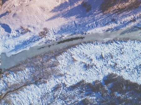 Aerial view of the winter rural landscape. Frozen creek on the meadow 写真素材
