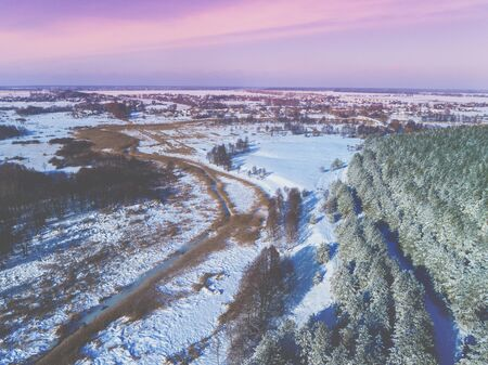 Top view of the winter rural landscape in the evening. Fields covered with snow, forest and frozen creek Zdjęcie Seryjne