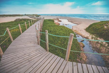 Wooden walkway on the sandy seashore on a sunny day. Porto, Portugal, Europe
