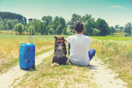 Man and dog are best friends travelers. Man and the dog sits together with travel suitcase back to the camera on a dirt road in the field in summer