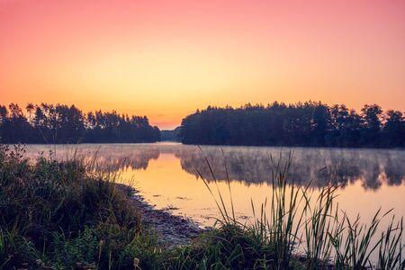 Magiczny świt nad jeziorem z pięknym odbiciem w wodzie. Spokojne jezioro wczesnym rankiem. Krajobraz przyrody