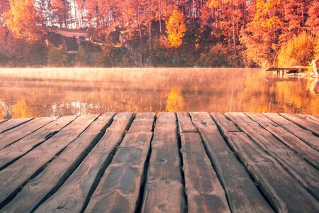 Magical sunrise over the lake. Wooden deck on the lakeshore. Serene lake in the early foggy morning. Nature landscape