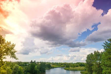 View from above of the countryside and river on a sunny day. Nature landscape with a beautiful cloudy sky. Summertime