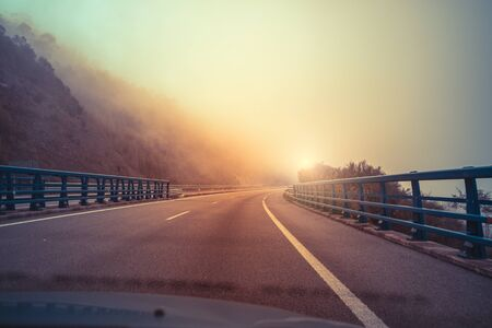 View of the overpass through the windshield. Beautiful misty morning landscape with a highway, bridge, and dramatic cloudy sky. Asturias, Spain