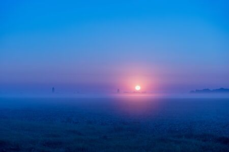 Rural landscape. Magical sunrise in the field on an early foggy morning. Minimalist landscape
