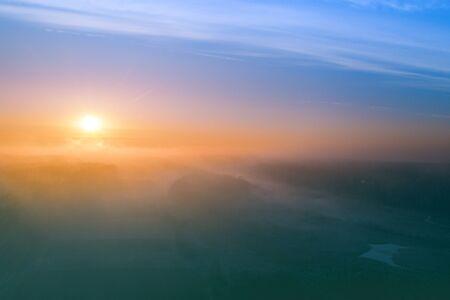 Früher nebliger Morgen. Sonnenaufgang in der Landschaft. Ländliche Landschaft im zeitigen Frühjahr. Luftaufnahme Standard-Bild