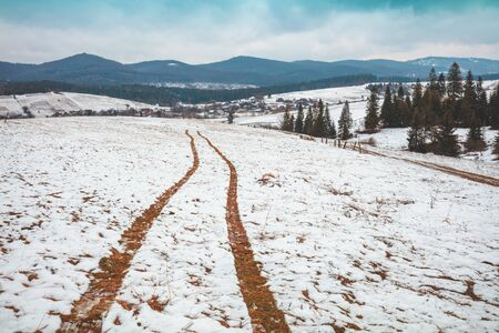 Traces of the car in the snow. Mountain landscape in the winter. The first snow in the Carpathians. Ukraine