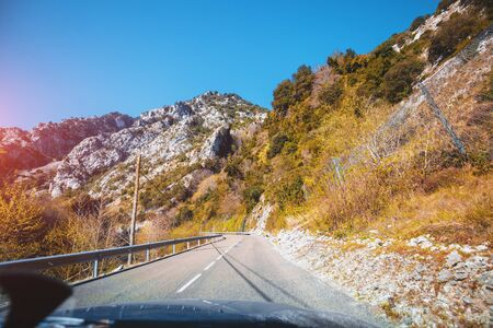 View of beautiful mountain landscape through the windscreen on a sunny day. Driving a car on mountain winding road in National park Picos de Europa. Cantabria, Spain, Europe