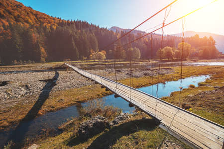 Wooden hanging rope bridge over mountain river
