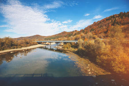 Panoramic view of mountain valley with river and bridge in autumn.