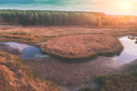 The winding brook flows through the meadow at sunset. Aerial view. Rural evening landscape