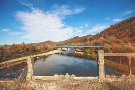 Panoramic view of mountain valley with river and bridge in autumn. View from destroyed bridge Imagens