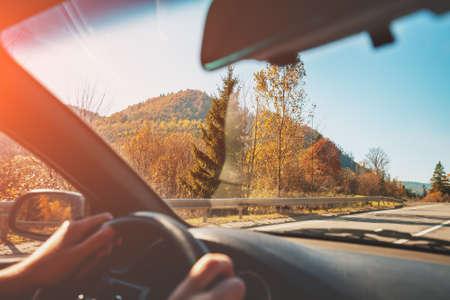 Driving a car on mountain road. Empty road on a sunny day. View from car of mountain landscape in autumn Imagens