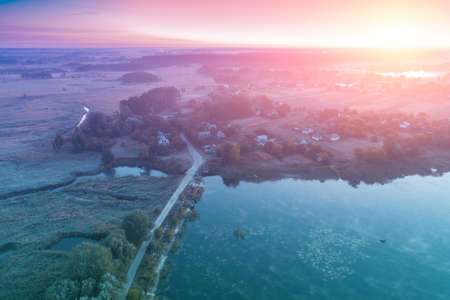 Magical sunrise in the countryside. Rural landscape in the morning. Aerial view of river, fields, and village
