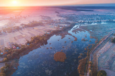 Magical sunset in countryside. Rural landscape in evening. Aerial view of river, fields and village Imagens