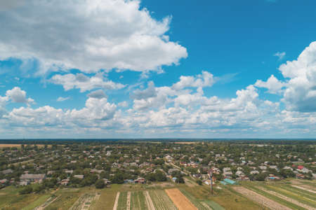 Summer rural landscape. Aerial view. View of the village and arable fields with beautiful sky