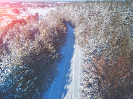 Country road in a pine forest. Winter nature. Snowy forest. View from above. Imagens