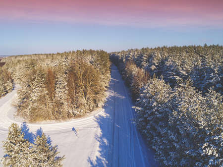 Country road in a pine forest. U-Turn. Winter nature. Snowy forest. View from above. Stock Photo