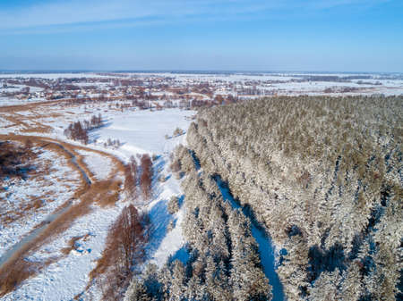 Winter rural landscape. Aerial view. Pine snowy forest in winter. Brook on the meadow. Nature background Imagens