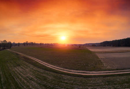 Orange sunset in the countryside. Rural landscape in early spring. Aerial view of plowed fields and dirt road