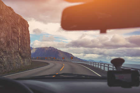 Driving a car on a mountain winding road. The road along mountains and fjord. Scandinavian landscape. Beautiful nature of Norway Foto de archivo