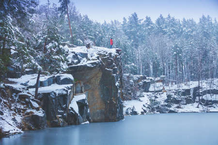 A man stays on the cliff edge on lakeshore covered with snow in winter and looks at the beautiful lake