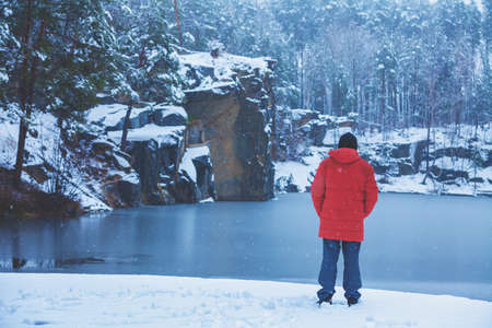 A man stays on a lakeshore, covered with snow in winter and looking at the beautiful lake back to the camera