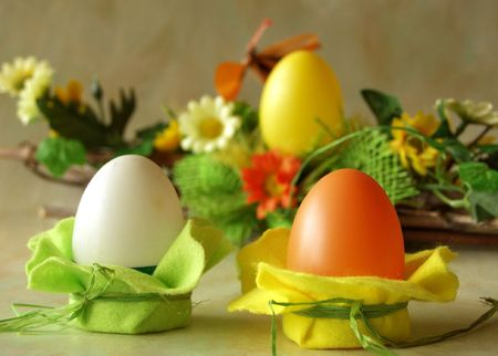Easter plastic eggs, table decoration with felt, spring flowers at background