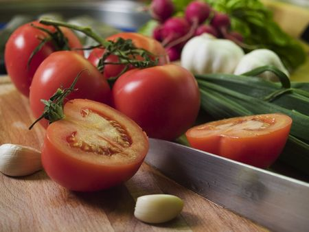 Cutting Tomatoes at kitchean board, vegetables at background photo