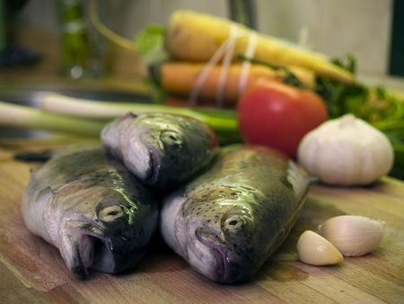 Three fresh trouts at kitchen cutting board, vegetables at background photo