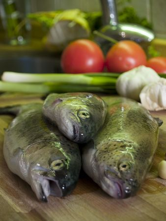 Three fresh trouts at kitchen cutting board, vegetables at background