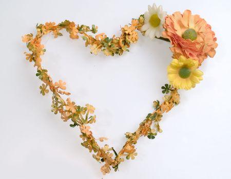 Coraz�n forma corona de flores de pl�stico de color naranja y amarillo, flores de primavera, fondo blanco Foto de archivo - 370068