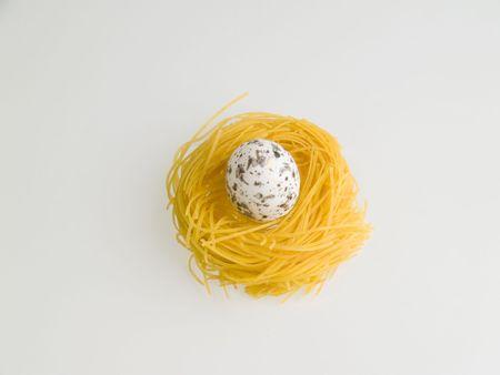Pasta nest with one egg, white background photo