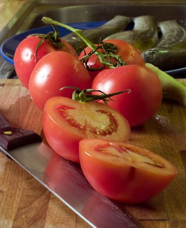 Tomatoes and knife at cutting board, trouts at background photo