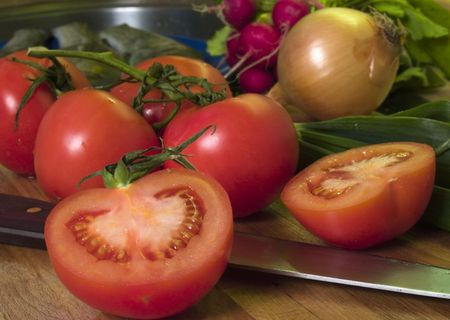 Vine tomatoes at cutting board, vegetables at background photo