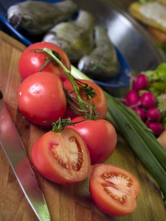 Tomatoes on cutting board, fish and vegetables at backround photo