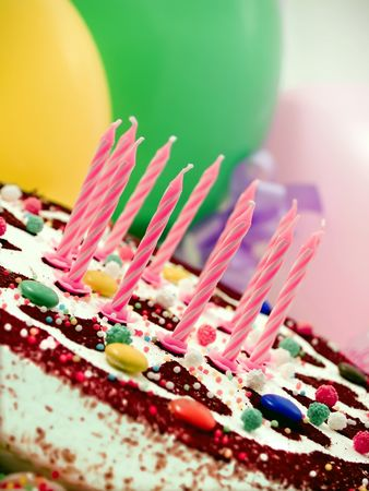 Colorful birthday cake, balloons at background