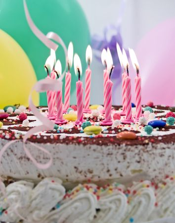 Birthday cake with eleven burning candles, balloons at background