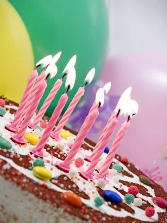 Eleven burning candles at birthday cake, baloons at background Stock Photo - 387189